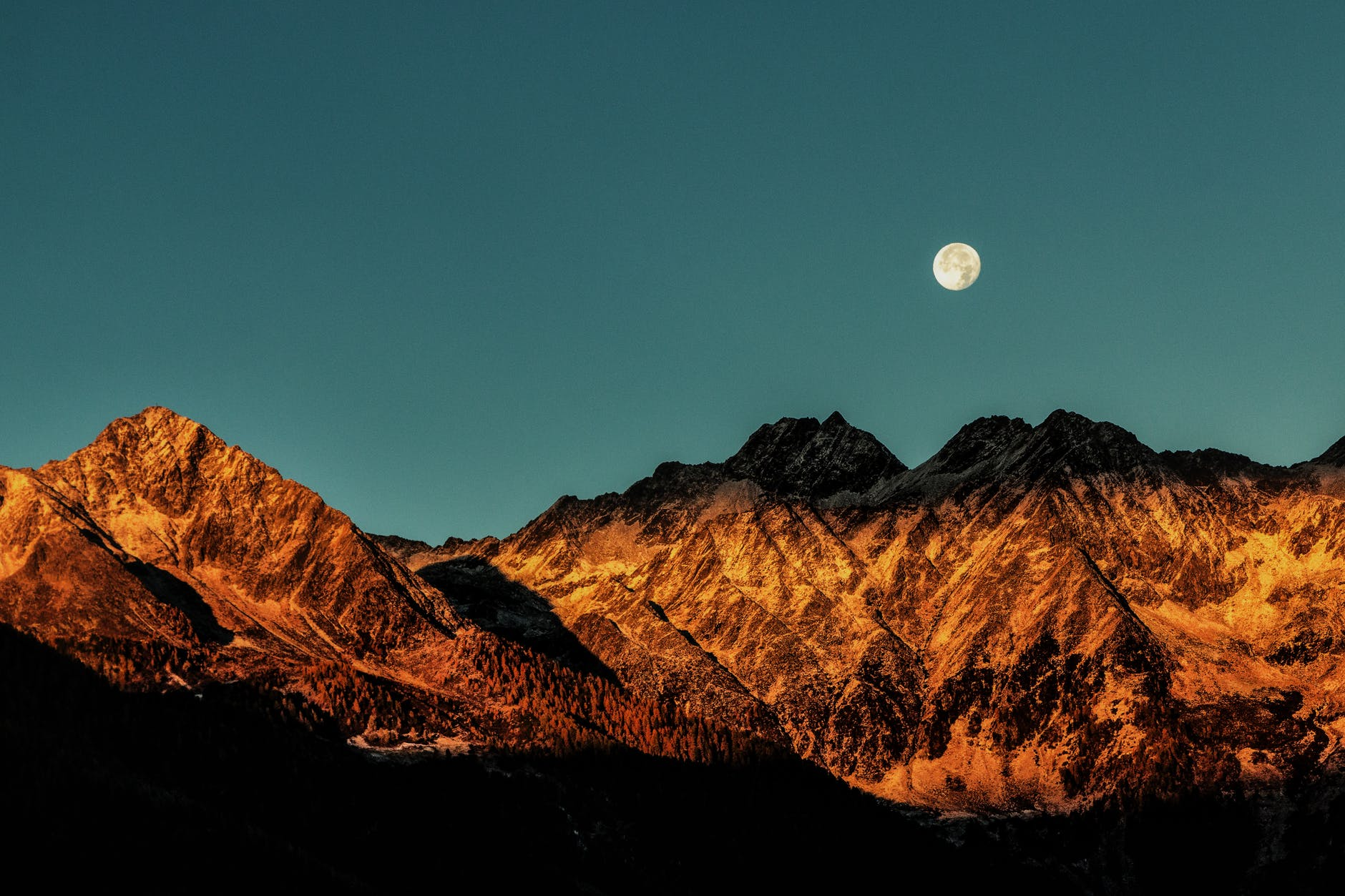 moon setting over mountains
